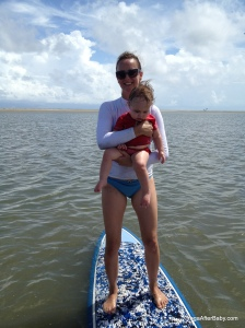 Practicing hold-your-one-year-old-steadily-while-on-paddleboard-asana.